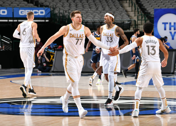 Luka Doncic and Jalen Brunson of the Dallas Mavericks hi-five during the game against the Denver Nuggets on January 25, 2021 at the American Airlines...