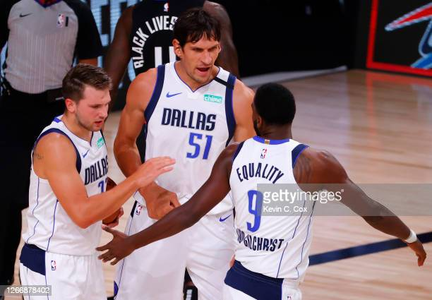 Luka Doncic, Boban Marjanovic and Michael Kidd-Gilchrist of the Dallas Mavericks celebrate a basket against the LA Clippers during the first quarter...