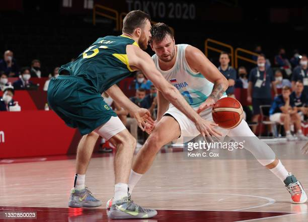 Luka Doncic of Team Slovenia and Nic Kay of Team Australia reach for a loose ball during the second half of the Men's Basketball Bronze medal game on...
