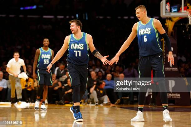 Luka Doncic of the Dallas Mavericks and Kristaps Porzingis of the Dallas Mavericks highfive during the second half against the Los Angeles Lakers at...