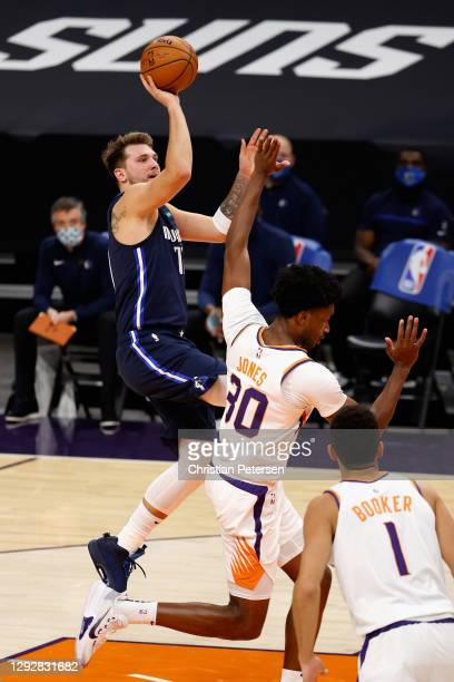 Luka Doncic of the Dallas Mavericks attempts a shot over Damian Jones of the Phoenix Suns during the first half of the NBA game at PHX Arena on...