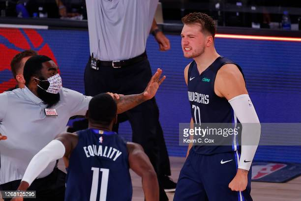 Luka Doncic of the Dallas Mavericks celebrates a game winning three point basket with teammates against the LA Clippers during overtime in Game Four...