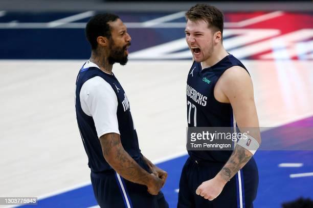 Luka Doncic of the Dallas Mavericks celebrates with James Johnson of the Dallas Mavericks after making the game-winning shot against the Boston...