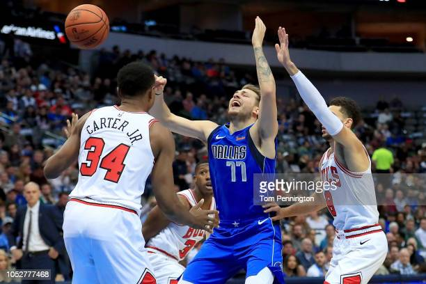 Luka Doncic of the Dallas Mavericks draws a foul against Wendell Carter Jr. #34 of the Chicago Bulls and Zach LaVine of the Chicago Bulls in the...