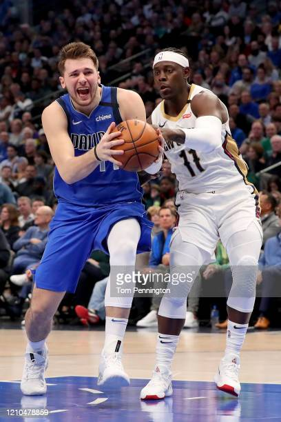 Luka Doncic of the Dallas Mavericks draws a foul from Jrue Holiday of the New Orleans Pelicans in the third quarter at American Airlines Center on...