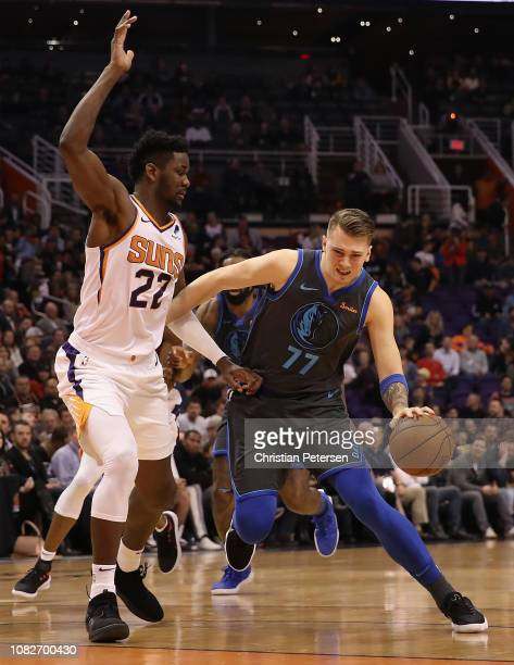 Luka Doncic of the Dallas Mavericks drives the ball past Deandre Ayton of the Phoenix Suns during the NBA game at Talking Stick Resort Arena on...