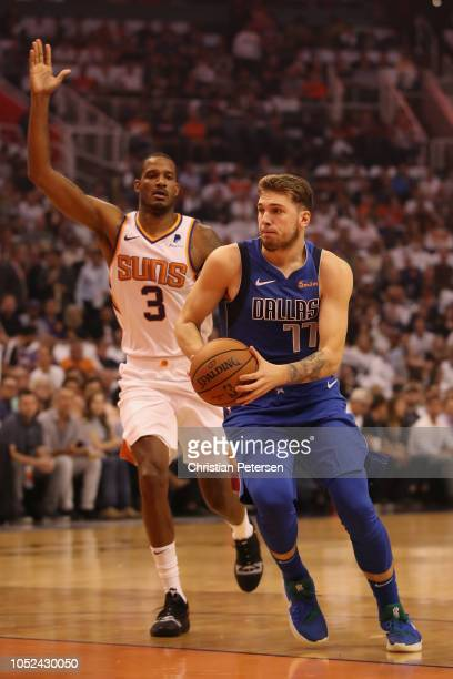 Luka Doncic of the Dallas Mavericks drives the ball past Trevor Ariza of the Phoenix Suns during the first half of the NBA game at Talking Stick...
