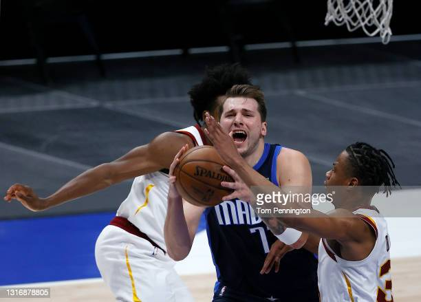 Luka Doncic of the Dallas Mavericks drives to the basket against Isaac Okoro of the Cleveland Cavaliers and Collin Sexton of the Cleveland Cavaliers...