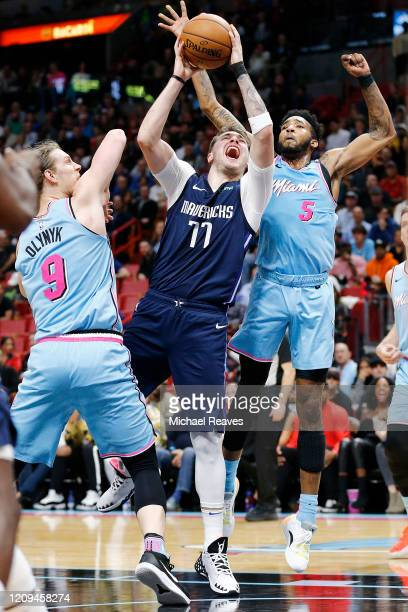 Luka Doncic of the Dallas Mavericks drives to the basket against Kelly Olynyk and Derrick Jones Jr. #5 of the Miami Heat during the first half at...