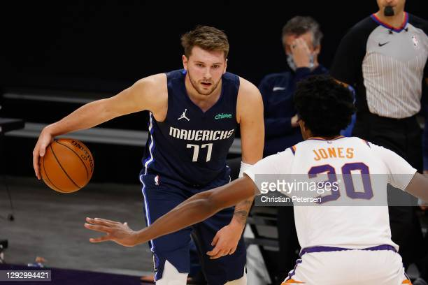 Luka Doncic of the Dallas Mavericks handles the ball against Damian Jones of the Phoenix Suns during the NBA game at PHX Arena on December 23, 2020...