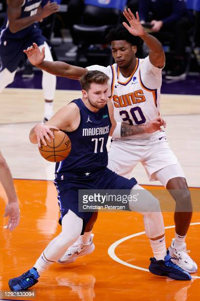 Luka Doncic of the Dallas Mavericks handles the ball guarded by Damian Jones of the Phoenix Suns during the first half of the NBA game at PHX Arena...
