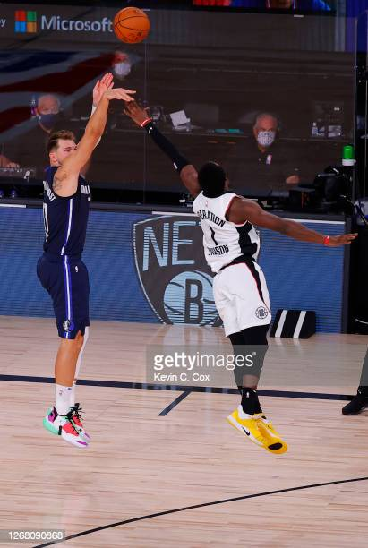 Luka Doncic of the Dallas Mavericks hits a game winning three point basket against Reggie Jackson of the LA Clippers during overtime in Game Four of...