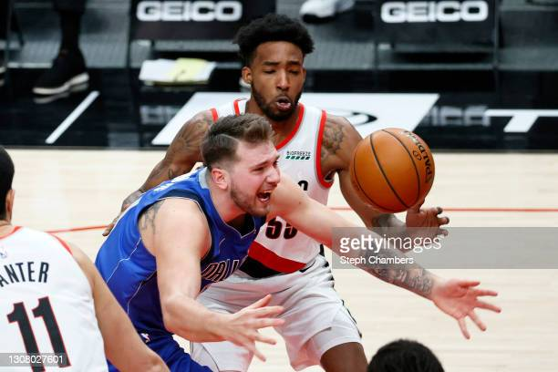 Luka Doncic of the Dallas Mavericks loses control of the ball while pressured by Derrick Jones Jr. #55 of the Portland Trail Blazers during the...