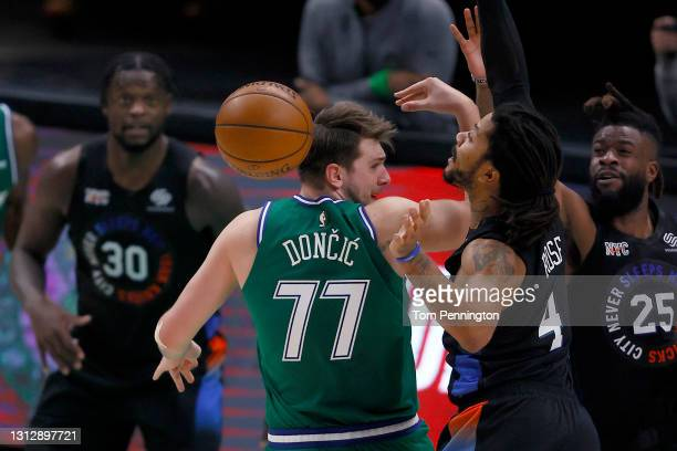 Luka Doncic of the Dallas Mavericks passes the ball against Derrick Rose of the New York Knicks and Reggie Bullock of the New York Knicks in the...
