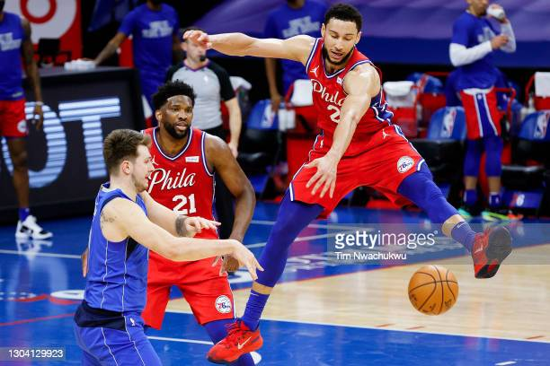Luka Doncic of the Dallas Mavericks passes under Ben Simmons of the Philadelphia 76ers during the third quarter at Wells Fargo Center on February 25,...