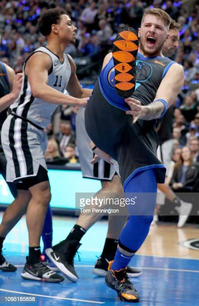 Luka Doncic of the Dallas Mavericks reacts after dunking the ball against Bryn Forbes of the San Antonio Spurs in the first half at American Airlines...