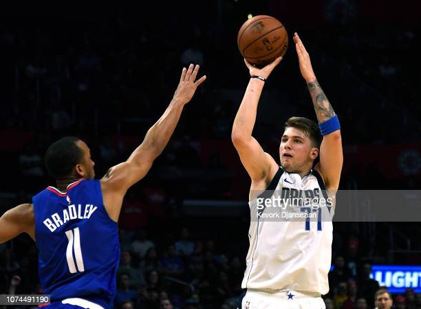 Luka Doncic of the Dallas Mavericks scores a three point basket against Avery Bradley of the Los Angeles Clippers during the second half at Staples...