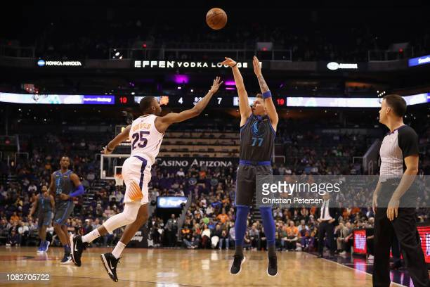 Luka Doncic of the Dallas Mavericks shoots over Mikal Bridges of the Phoenix Suns during the NBA game at Talking Stick Resort Arena on December 13...