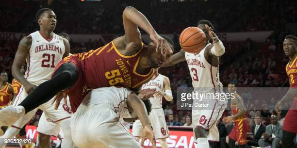 Luka Garza of the Iowa Hawkeyes falls on Kameron McGusty of the Oklahoma Sooners during the first half of a NCAA college basketball game at the Lloyd...
