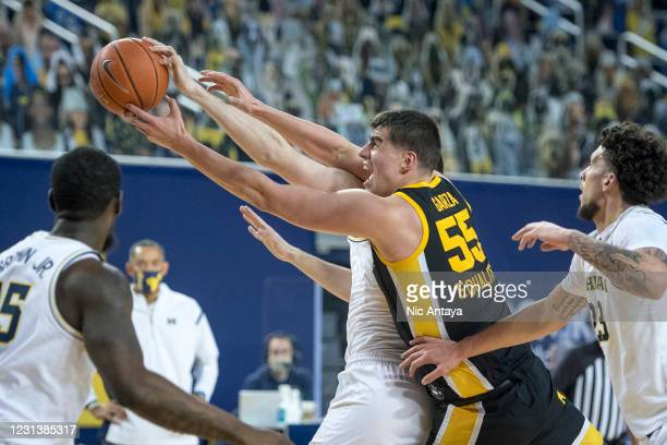 Luka Garza of the Iowa Hawkeyes reaches for a rebound against Hunter Dickinson of the Michigan Wolverines during the first half at Crisler Arena on...