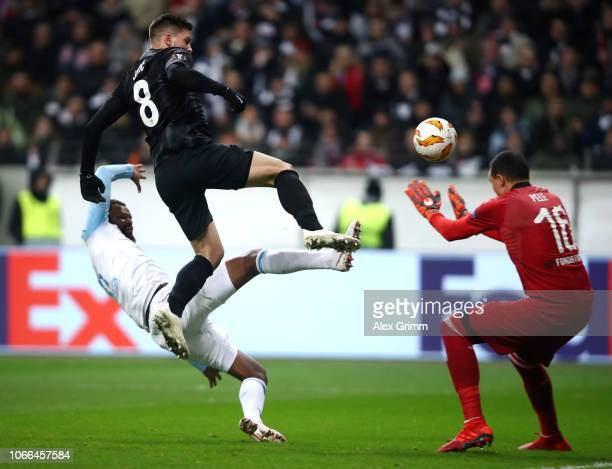Luka Jovic of Eintracht Frankfurt scores his team's fourth goal past Yohann Pele of Marseille while he is being challenged by Rolando of Marseille...