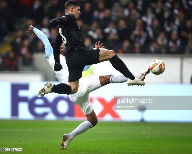 Luka Jovic of Eintracht Frankfurt scores his team's fourth goal while he is being challenged by Rolando of Marseille during the UEFA Europa League...