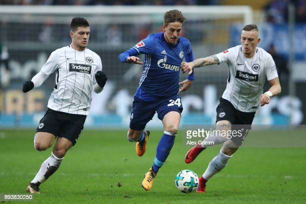 Luka Jovic of Frankfurt Bastian Oczipka of Schalke and Marius Wolf of Frankfurt fight for the ball during the Bundesliga match between Eintracht...