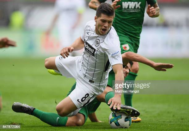 Luka Jovic of Frankfurt is challenged by Rani Khedira of Ausgburg during the Bundesliga match between Eintracht Frankfurt and FC Augsburg at...