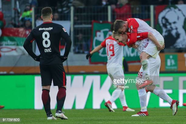Luka Jovic of Frankfurt looks dejected and Martin Hinteregger of Augsburg and Daniel Baier of Augsburg celebrate their team`s goal during the...