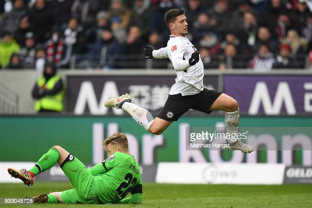 Luka Jovic of Frankfurt runs over goalkeeper Florian Mueller of Mainz during the Bundesliga match between Eintracht Frankfurt and 1 FSV Mainz 05 at...