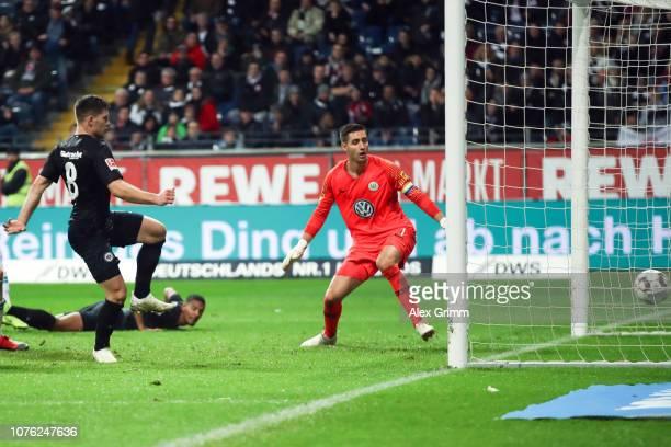 Luka Jovic of Frankfurt scores his team's first goal past goalkeeper Koen Casteels of Wolfsburg during the Bundesliga match between Eintracht...