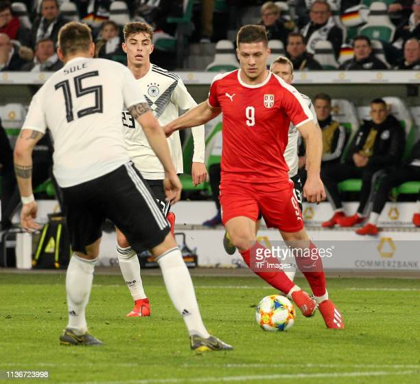 Luka Jovic of Serbia and Niklas Suele of Germany battle for the ball during the International Friendly match between Germany and Serbia at Volkswagen...