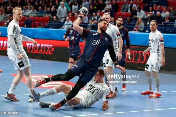 Luka Karabatic of Paris Saint Germain is shooting the ball against Nikola Bilyk of THW Kiel during the Champions League match between Paris Saint...
