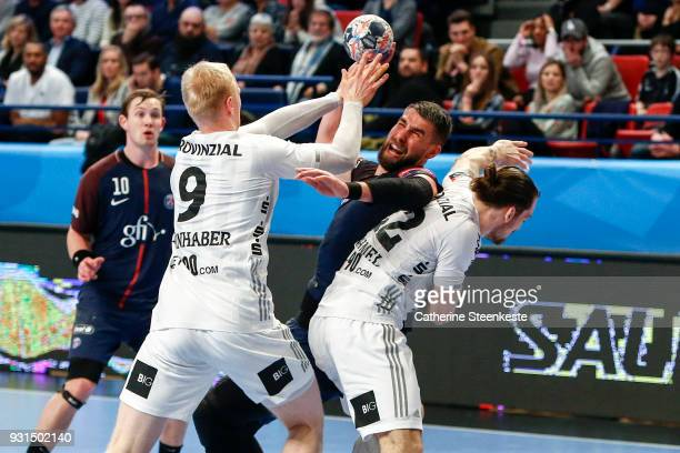 Luka Karabatic of Paris Saint Germain is trying to shoot the ball against Sebastian Firnhaber and Ole Rahmel of THW Kiel during the Champions League...