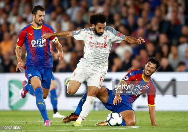 Luka Milivojevic and James Tomkins of Crystal Palace challenge Mohamed Salah of Liverpool during the Premier League match between Crystal Palace and...