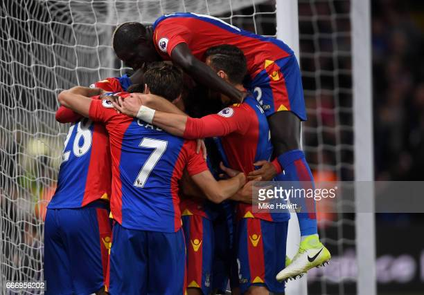 Luka Milivojevic of Crystal Palace celebrates as he scores their third goal from a penalty with team mates during the Premier League match between...