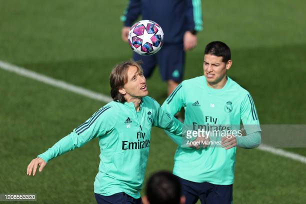Luka Modric and James Rodriguez compete for the ball during a training session ahead of their UEFA Champions League round of 16 first leg match...