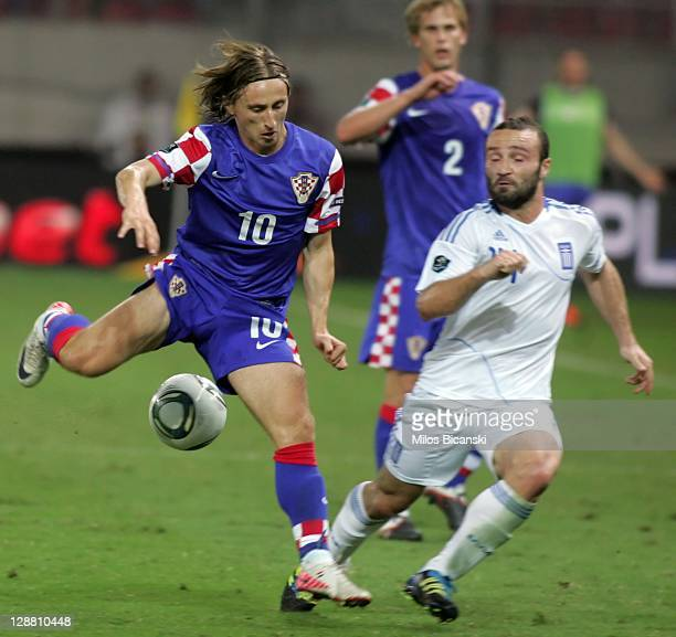 Luka Modric of Croatia is challenged by Dimitris Salpingidis of Greece during the UEFA Euro 2012 Qualifying round group F match between Greece and...