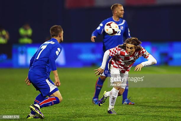 Luka Modric of Croatia is challenged by Johann Gudmundsson of Iceland during the FIFA 2014 World Cup Qualifier playoff second leg match between...