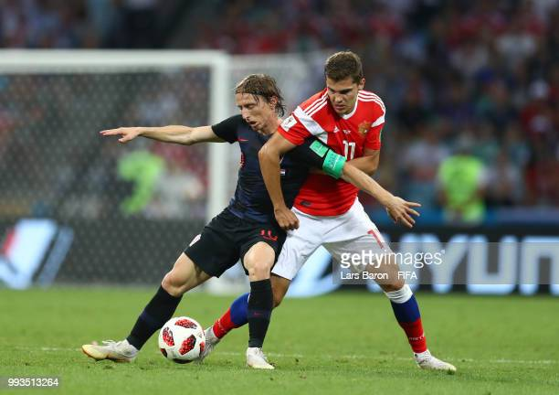 Luka Modric of Croatia is challenged by Roman Zobnin of Russia during the 2018 FIFA World Cup Russia Quarter Final match between Russia and Croatia...