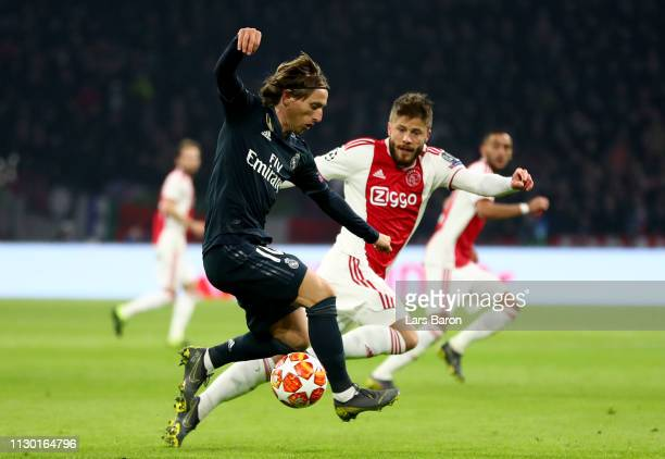 Luka Modric of Madrid is challenged by Lasse Schoene of Amsterdam during the UEFA Champions League Round of 16 First Leg match between Ajax and Real...