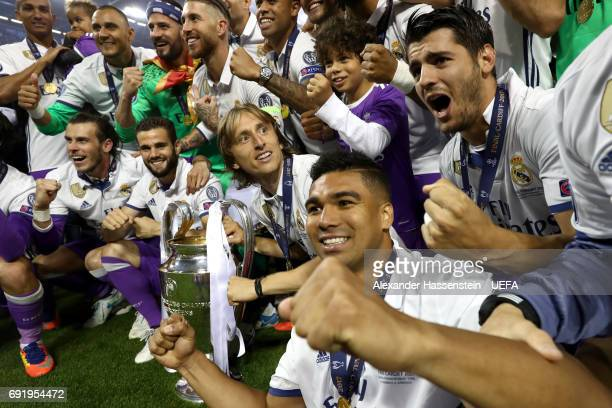 Luka Modric of Real Madrid and Casemiro of Real Madrid celebrate with the trophy and their Real Madrid team mates after the UEFA Champions League...