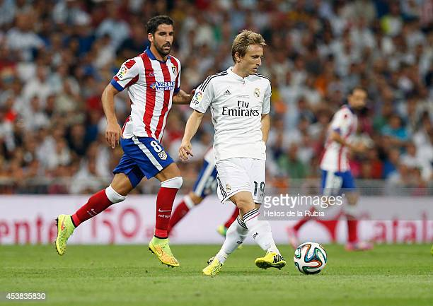Luka Modric of Real Madrid and Raul Garcia of Atletico de Madrid compete for the ball during the Supercopa first leg match between Real Madrid and...