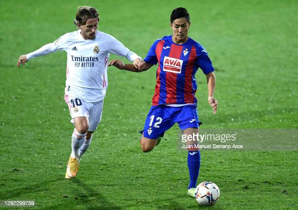 Luka Modric of Real Madrid battles for possession with Yoshinori Muto of SD Eibar during the La Liga Santander match between SD Eibar and Real Madrid...