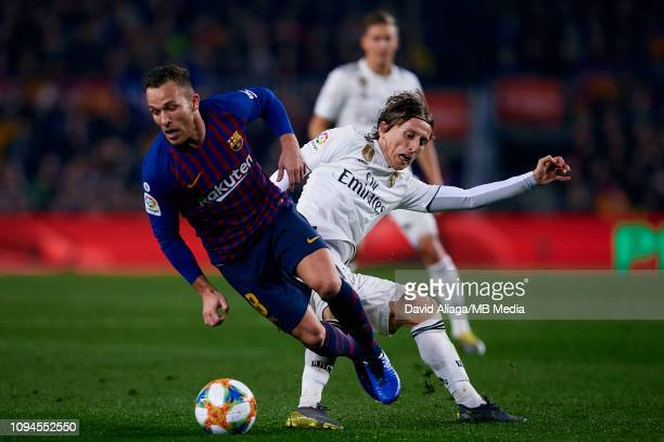 Luka Modric of Real Madrid CF competes for the ball with Arthur Henrique Ramos de Oliveira Melo of FC Barcelona during the Copa del Semi Final match...