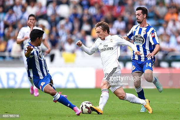 Luka Modric of Real Madrid CF competes for the ball with Juanfran Moreno and Isaac Cuenca of RC Deportivo La Coruna during the La Liga match between...