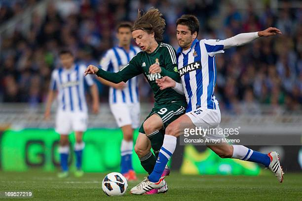 Luka Modric of Real Madrid CF competes for the ball with Markel Bergara of Real Sociedad during the La Liga match between Real Sociedad de Futbol and...