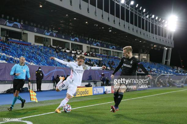 Luka Modric of Real Madrid CF competes for the ball with Oscar Wendt of VfL Borussia Monchengladbach during the UEFA Champions League Group B stage...