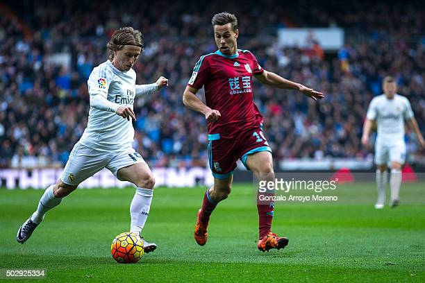 Luka Modric of Real Madrid CF competes for the ball with Sergio Canales of Real Sociedad de Futbol during the La Liga match between Real Madrid CF...