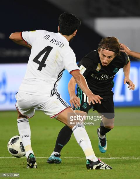 Luka Modric of Real Madrid CF dribbles the ball to beat Mohamed Ayed of Al Jazira during the FIFA Club World Cup semifinal match between Al Jazira an...